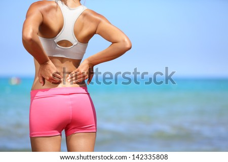 Back pain. Athletic woman in pink sportswear standing at the seaside rubbing the muscles of her lower back, cropped torso portrait. - stock photo
