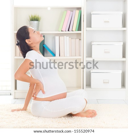 Back pain. Eight months pregnant Asian woman holding her back while sitting on a floor at home.