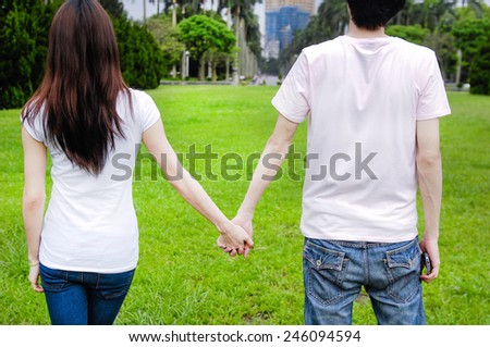 Back People in love with couple holding hands in park.  - stock photo