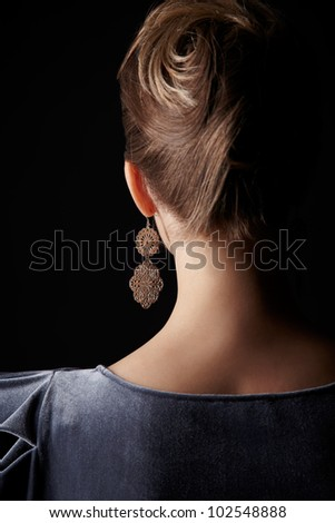back portrait of beautiful young brunette woman on black - stock photo
