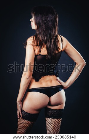 Back portrait of sexy woman posing in black lingerie over black background. The beautiful young sexy girl in stockings poses in studio on black background. Bdsm Concept. Front view.  - stock photo
