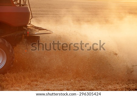 Back rear of harvester on the field with dust
