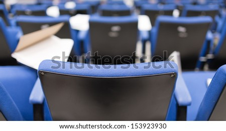 Back row perspective view of lecture chair in conferences room - stock photo