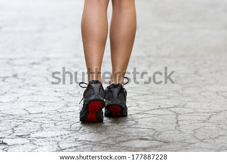 back shot of young lady with fitness shoes in act to walking ,running on a broken fashion road - stock photo