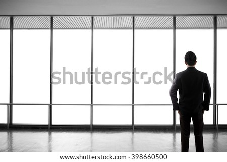 Back side business man standing and looking at a white blank of office window. Clipping path on window. - stock photo