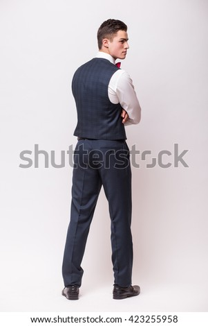 Back side Handsome young businessman in suit standing against white background - stock photo