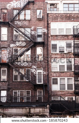 Back Side Of A Brick Apartment Building In Manhattan, Showing The Fire  Escape And Graffiti