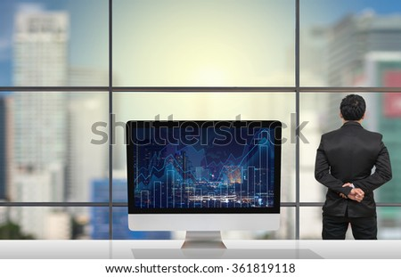 Back side of Businessman looking at citiy out off windows glass with Computer show Trading graph on the cityscape at night and world map on the table in meeting room,Business financial concept - stock photo