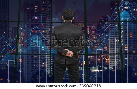 Back side of Businessman looking at Trading graph on the cityscape at night and world map background,Business financial concept - stock photo