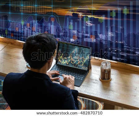 Back side of Businessman sitting and using computer laptop showing stock market chart beside the windows glass over the trading graph on cityscape background, Business financial and trading concept