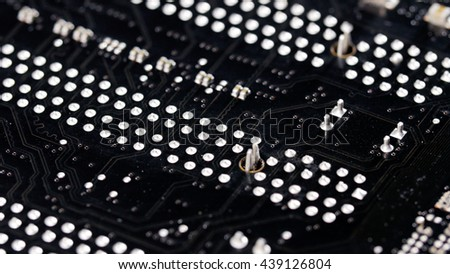 Back side of computer mainboard circuit board closeup background - stock photo