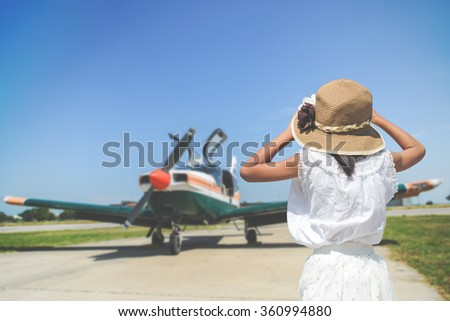 Back side of girl looking at the the sky with small plane background in sunny day. - stock photo