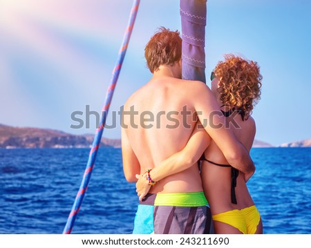 Back side of happy young couple standing on the deck of luxury sail boat, romantic date in sunny summer day, enjoying each other concept - stock photo