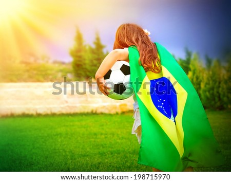 Back side of little active football fan running on the green grass field with ball, young supporter of Brazilian football team with national flag  - stock photo