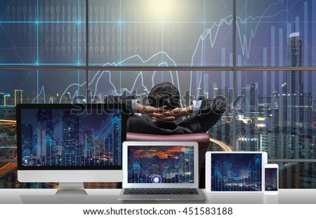 Back side of sitting businessman who is looking at city out off windows glass with Computer set show Trading graph on the cityscape and world map background on the table, Business financial concept - stock photo