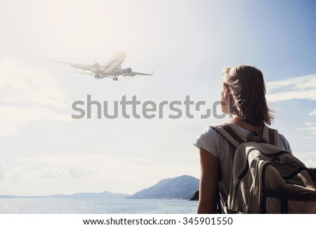 Back side of traveler girl looking at the flying plane above the sea, travel and active lifestyle concept