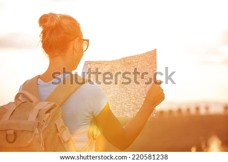 Back side of traveler girl searching right direction on map, bright orange sunset light, traveling along Europe, freedom and active lifestyle concept - stock photo