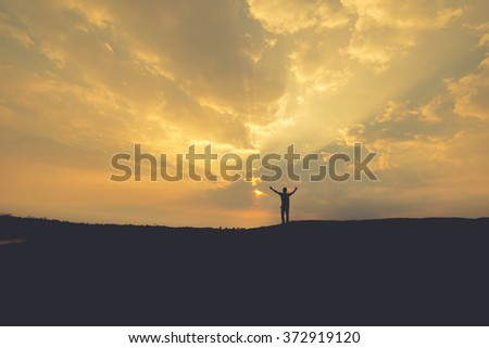 Back side of traveler man searching right direction on map, bright orange sunset light, traveling along Europe, freedom and active lifestyle concept overcome
