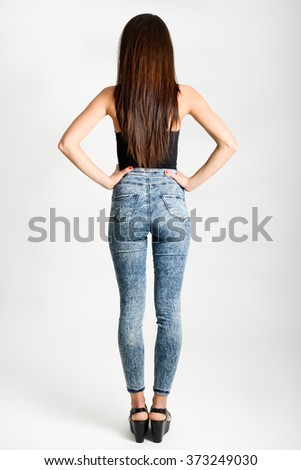 Back side of woman wearing high-waisted jeans. Studio shot. Girl with on white background - stock photo