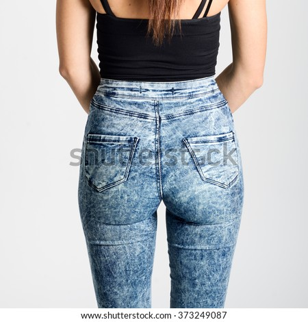 Back side of woman wearing high-waisted jeans. Studio shot. Girl with on white background