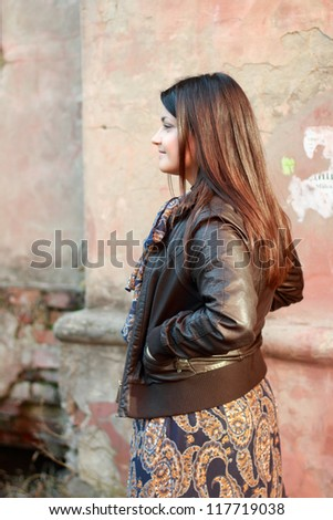 Back side of young brunette woman portrait in autumn color