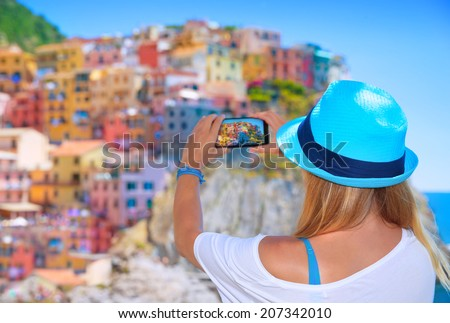 Back side of young woman taking picture of beautiful colorful old Italian buildings, happy travel to Europe, summer vacation concept - stock photo