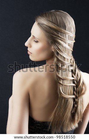back side portrait of a fashion woman with long hair and old style and creative hairstylish, she is turned at her left, her left arm is bent and her eyes are closed - stock photo