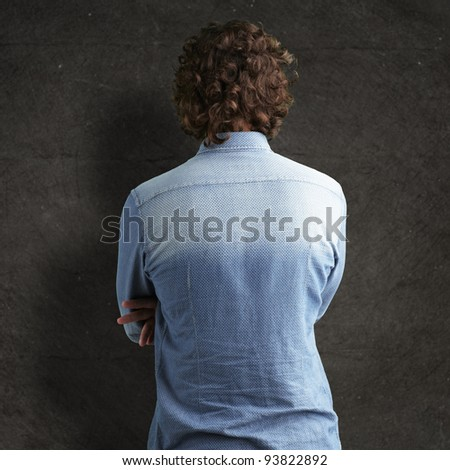 Back side view of a man against a grunge wall - stock photo