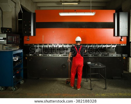 back side view of a worker, standing, wearing red overalls, and a white protective helmet operating an industrial machinery, painted in red and black, with a control panel and a table next to it - stock photo