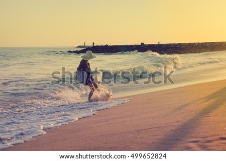 Back side view of woman in summer hat and beach bag playing with waves on the sunny ocean tropic outdoors background