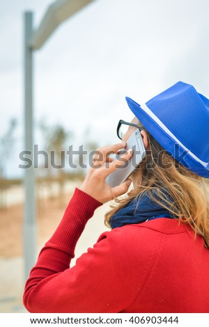 Back side view of young business lady making a call on her smart phone on a bright day outdoors background. Closeup photo
