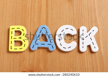 BACK, spell by woody puzzle letters with woody background - stock photo