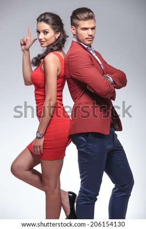 back to back man and woman secret agents posing in studio - stock photo