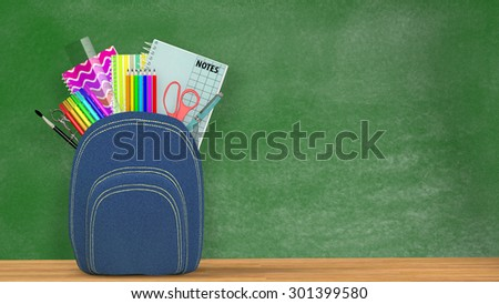 Back to school. A blue Satchel full of school supplies in front of a green blackboard into a classroom.Copy space available. - stock photo