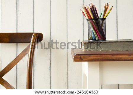 Back to school. A chair, a table, a book and some pencils. - stock photo