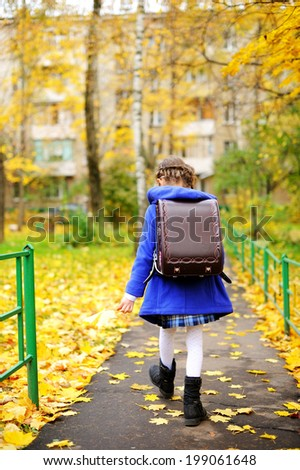 Back to school - adorable brunette girl in blue coat and blue-white school uniform having fun with yellow maple  leaves in the autumn park