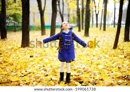 Back to school - adorable brunette girl in blue coat and blue-white school uniform having fun with yellow maple  leaves in the autumn park - stock photo