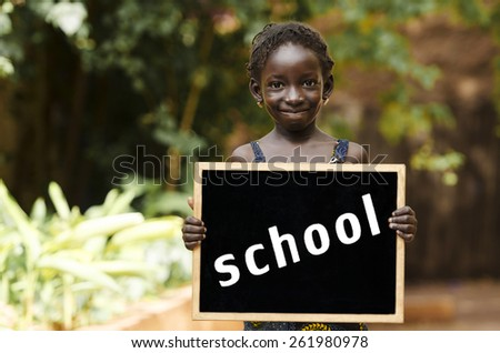 Back to School - African Child Holding Chalkboard Education. An African girl holding a blackboard, with plenty of copy space. - stock photo