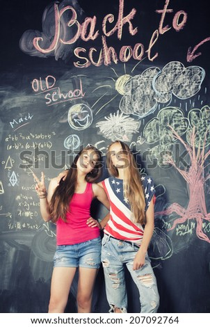 back to school after summer vacations, two teen girls in classroom with blackboard painted - stock photo