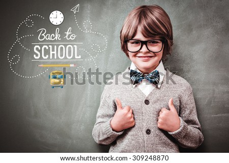 back to school against little boy gesturing thumbs up against blackboard - stock photo