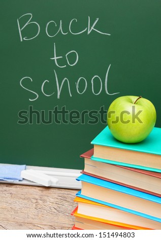Back to school. An alarm clock and other school accessories against a school board.