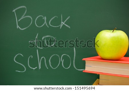 Back to school. An apple and books against a school board.