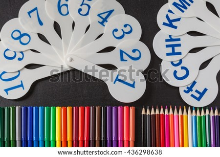 Back to school background with a lot of colorful felt-tip pens and colorful pencils and cards of numerals from one to ten and consonant letters of alphabet on the black school chalkboard - stock photo