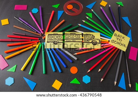 "Back to school background with a lot of colorful felt-tip pens and colorful pencils in circles, titles ""Back to school"" and drawing of school bus drawn on the yellow pieces of paper on the chalkboard - stock photo"