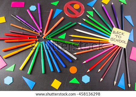 "Back to school background with a lot of colorful felt-tip pens and colorful pencils in circles and  title ""Back to school"" written on the yellow pieces of paper on the black school chalkboard - stock photo"