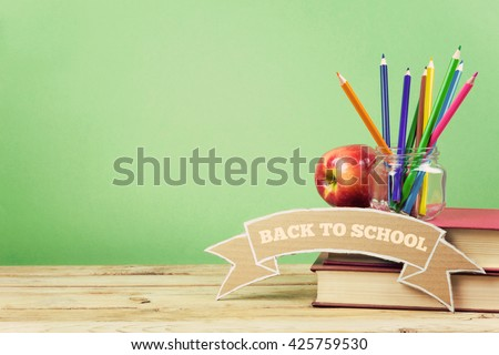 Back to school background with books, pencils and apple on wooden table.