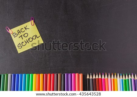 "Back to school background with colorful felt tip pens, pencils and  title ""Back to school"" written on yellow piece of paper on the black school chalkboard - stock photo"