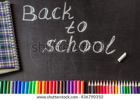 "Back to school background with colorful felt tip pens, pencils, notebook and the title ""Back to school"" written by white chalk on the black school chalkboard - stock photo"