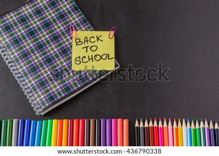 "Back to school background with colorful felt tip pens, pencils, notebook and  title ""Back to school"" written on yellow piece of paper on the black school chalkboard - stock photo"