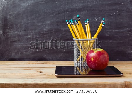 Back to school background with tablet, pencils and apple over chalkboard - stock photo